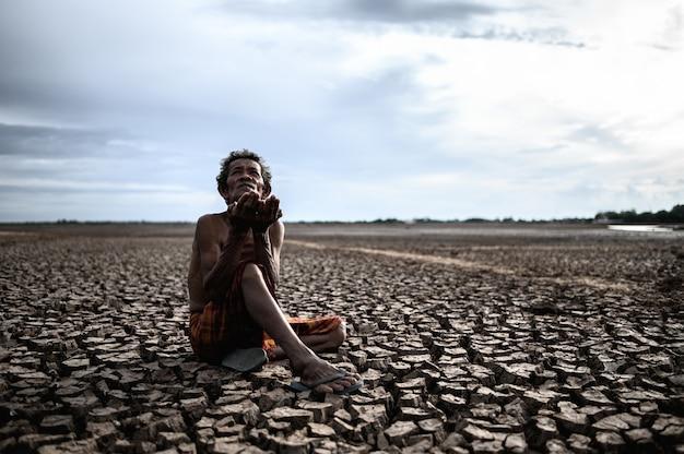 Starszy mężczyzna siedział z prośbą o deszcz w porze suchej, globalne ocieplenie