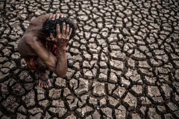 Starszy mężczyzna siedział zgięty w kolanach na suchej podłodze, a ręce trzymał głowę, globalne ocieplenie