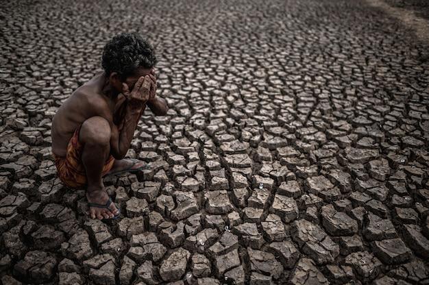 Starszy mężczyzna siedział zgięty w kolanach na suchej ziemi i ręce zamknięte na twarzy, globalne ocieplenie