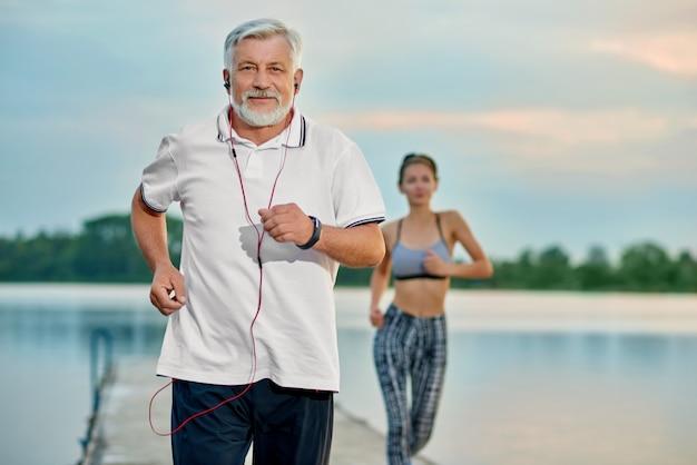 Starszy mężczyzna słucha muzyki, biega blisko jeziora w wieczór.