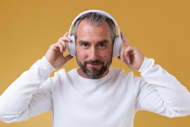 Starszy mężczyzna słucha muzyki przez słuchawki