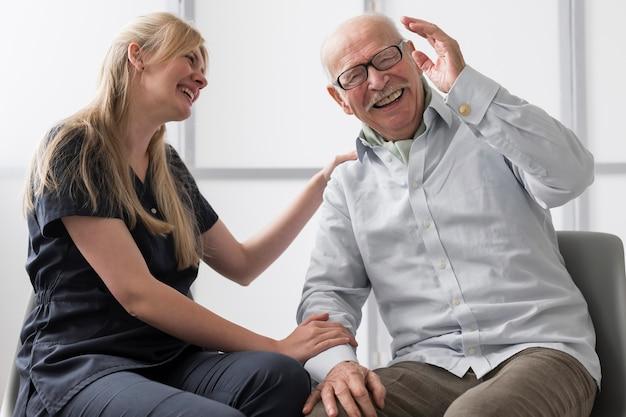 Starszy mężczyzna śmiejąc się z pielęgniarką w domu opieki