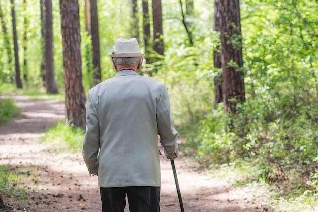 Starszy mężczyzna spaceru w lesie