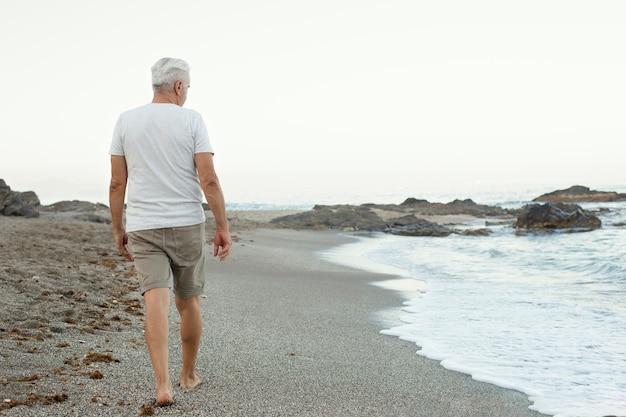 Starszy mężczyzna spacerujący samotnie po plaży