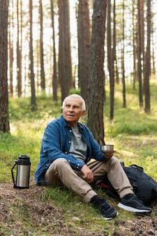 Starszy mężczyzna spędza czas na łonie natury podczas podróży z plecakiem