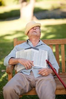 Starszy mężczyzna śpi na ławce