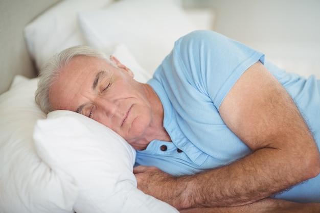 Starszy mężczyzna śpi na łóżku