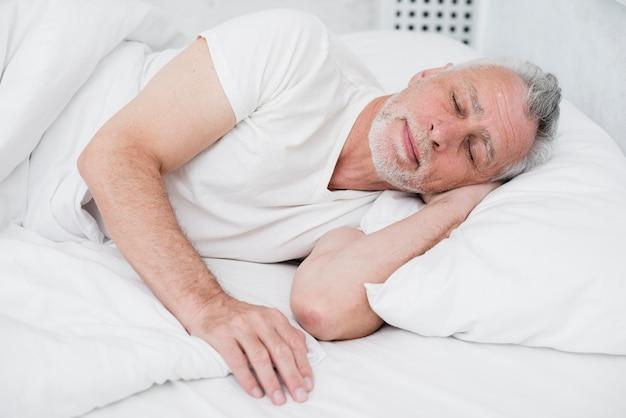 Starszy mężczyzna śpi w białym łóżku