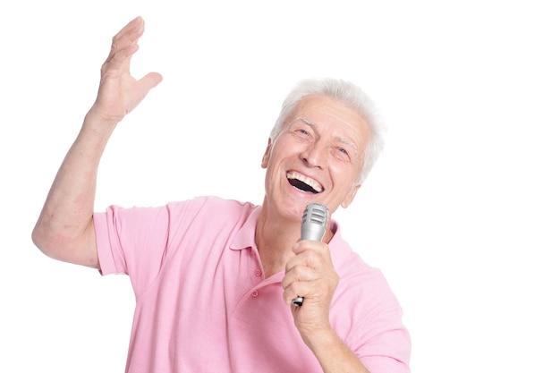 Starszy mężczyzna śpiewa do mikrofonu na białym tle