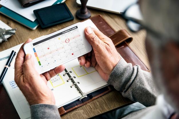 Starszy mężczyzna sprawdza jego kalendarz