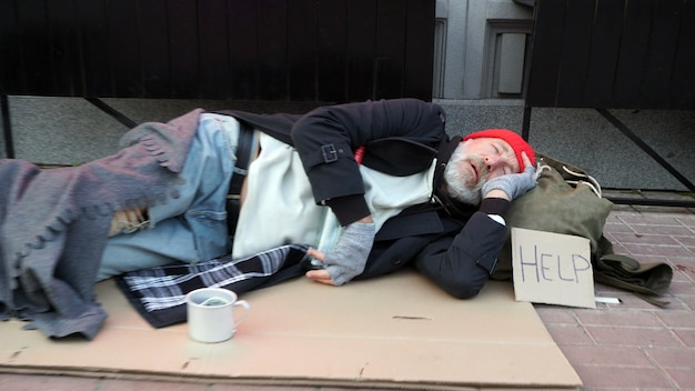 Starszy mężczyzna, starzec, żebrak, marznący na ulicy, pijący ciepłą wodę, aby się ogrzać, spał na tekturze na ulicy