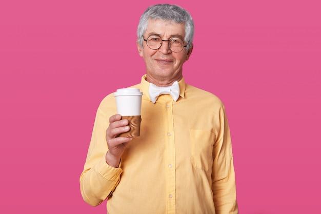 Starszy mężczyzna stoi z kawą na różowej ścianie.