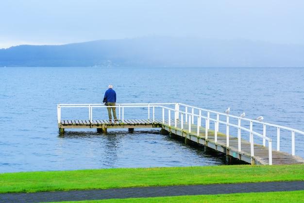 Starszy mężczyzna stojący na moście podziwiając piękno jeziora taupo rano, wyspa południowa nowej zelandii