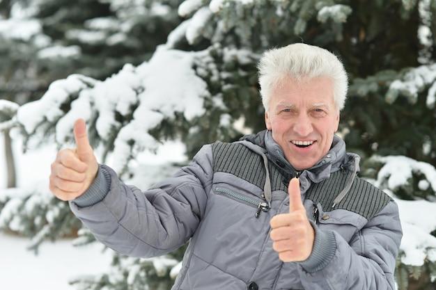 Starszy mężczyzna stojący na zewnątrz w zimie z kciukami w górę