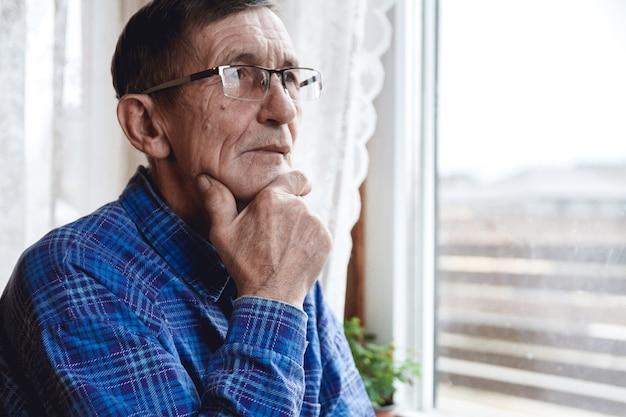 Starszy mężczyzna stojący przy oknie