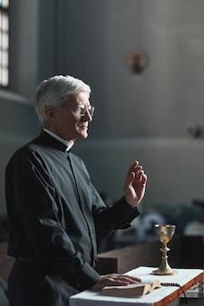 Starszy mężczyzna stojący z biblią przed ołtarzem i modlący się
