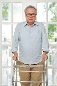 Starszy mężczyzna stojący z walkerem w domu