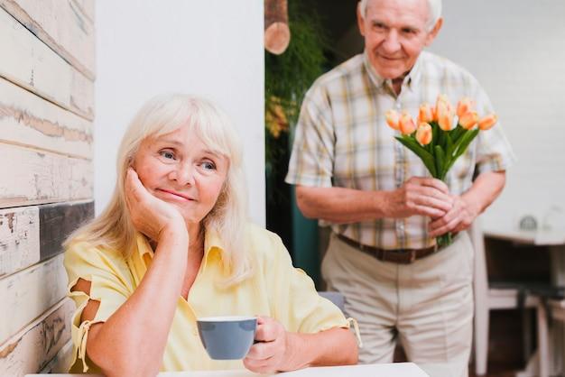 Starszy mężczyzna stojący za ukochaną z kwiatami