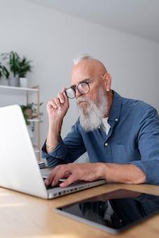 Starszy mężczyzna studiujący z laptopem średni strzał