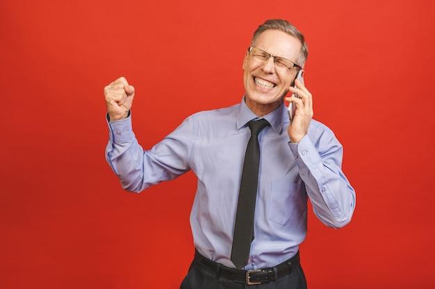 Starszy mężczyzna świętuje szalony i zdumiony sukcesem z podniesionymi rękami i otwartymi oczami krzyczącymi z podniecenia. koncepcja zwycięzcy. korzystanie z telefonu