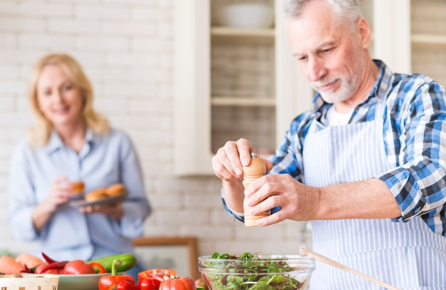 Starszy mężczyzna szlifowanie pieprz do sałatki i jej żona ciesząc się babeczki w tle w kuchni