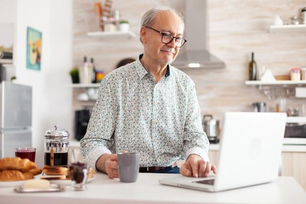 Starszy mężczyzna szuka online przepis za pomocą laptopa w nowoczesnej kuchni podczas śniadania. osoba w podeszłym wieku na emeryturze pracująca w domu, pracująca na odległość za pomocą zdalnej komunikacji internetowej o pracy w internecie
