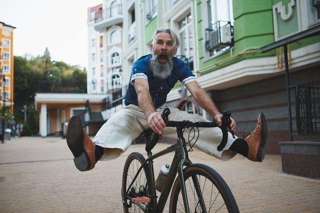 Starszy mężczyzna szuka śmieszne jazda konna rower krzyczy podnosząc nogi w powietrzu