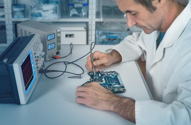 Starszy mężczyzna technik pracuje w zakładzie naprawy sprzętu