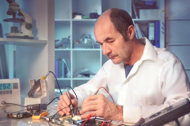 Starszy mężczyzna technik testuje sprzęt elektroniczny, stonowanych