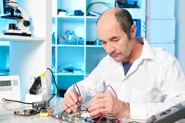 Starszy mężczyzna technika naprawia płytkę drukowaną