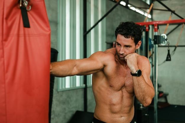 Starszy mężczyzna trenuje boks w gym