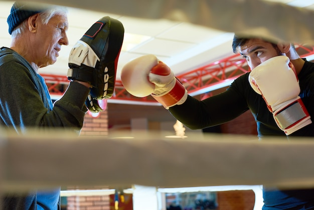 Starszy mężczyzna trenuje młodego boksera