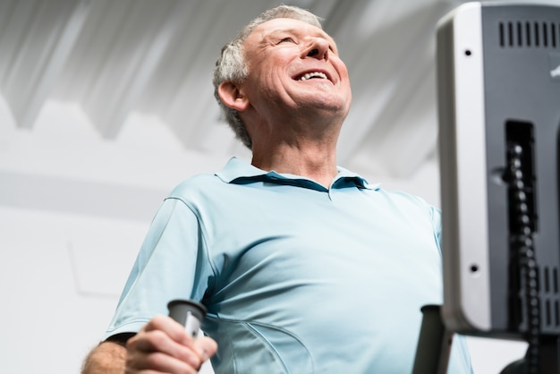 Starszy mężczyzna trenuje na przecinającym trenerze przy gym