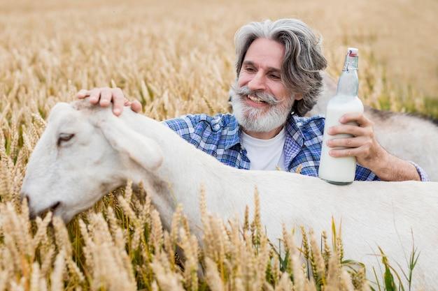 Starszy mężczyzna trzyma butelkę koziego mleka