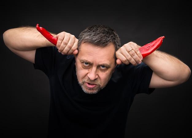 Starszy mężczyzna trzyma dwa czerwone papryczki chili