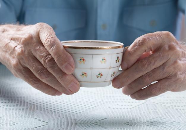 Starszy mężczyzna trzyma filiżankę herbata w ich rękach przy stołowym zakończeniem
