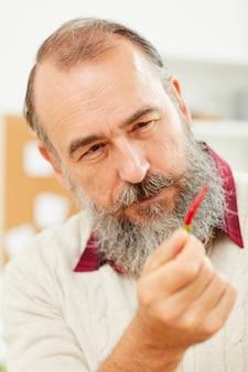 Starszy mężczyzna trzyma ostrą paprykę