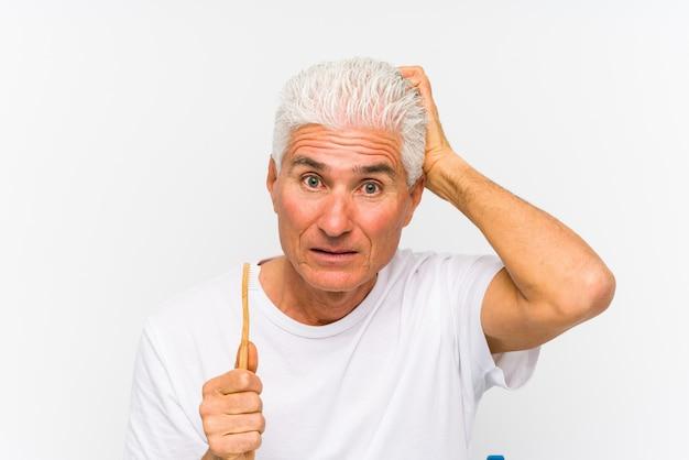 Starszy mężczyzna trzyma szczoteczkę do zębów będąc w szoku, przypomniała sobie ważne spotkanie