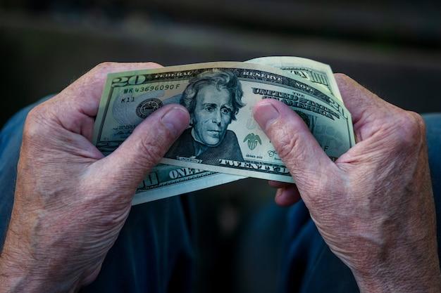 Starszy mężczyzna trzyma w ręce dolary amerykańskie, 20 dolarów uwaga w ręce emeryta