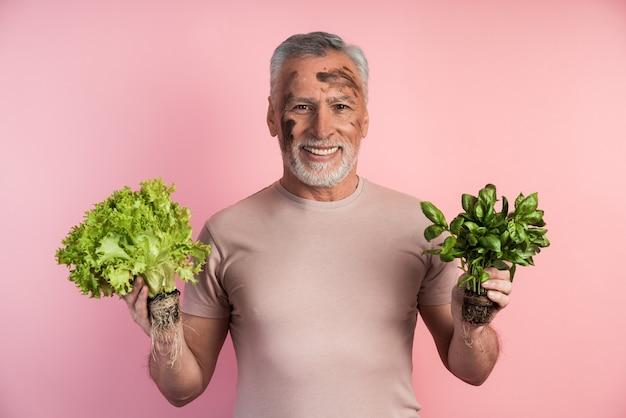 Starszy mężczyzna trzyma w rękach zieleninę i uśmiecha się szczerze