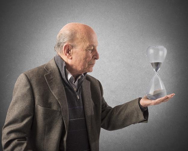 Starszy mężczyzna trzyma w ręku klepsydrę