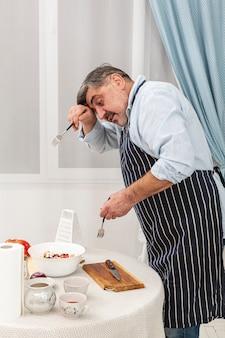 Starszy mężczyzna trzyma widelce do sałatki