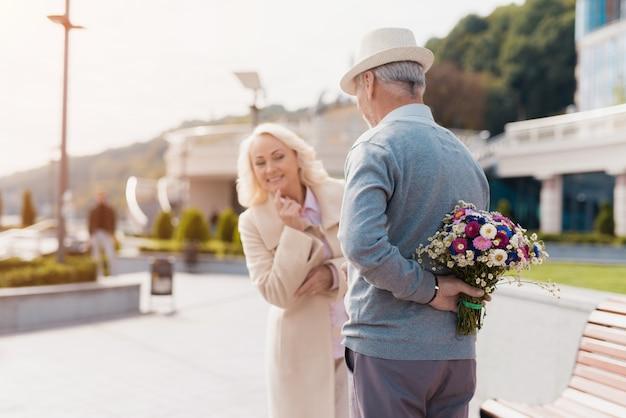 Starszy mężczyzna trzyma za plecami bukiet kwiatów.