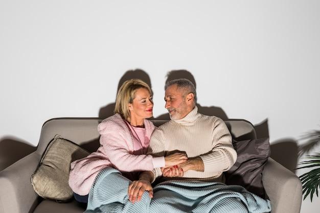 Starszy mężczyzna trzymając się za ręce z kobietą i oglądanie telewizji na kanapie