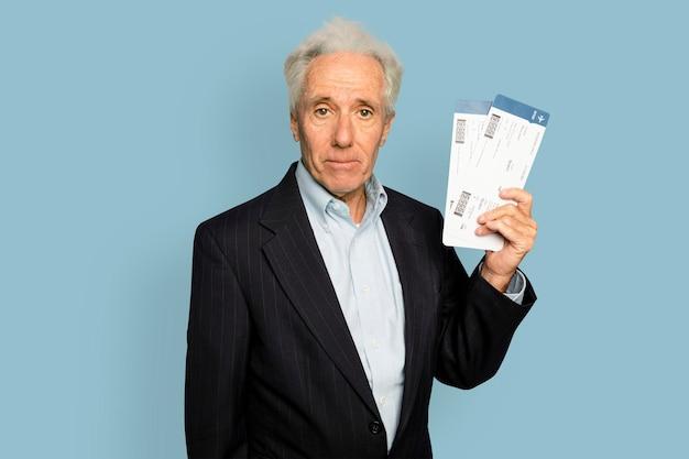 Starszy mężczyzna trzymający bilety lotnicze na podróż służbową