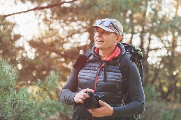 Starszy mężczyzna turysta robi zdjęcie dzikiej przyrody w lesie