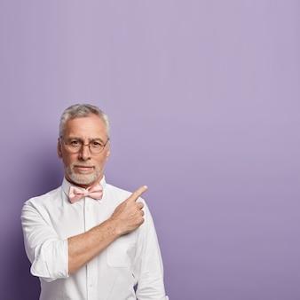 Starszy mężczyzna ubrany w białą koszulę i różową muszkę