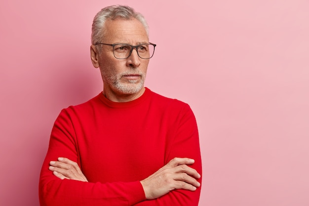 Starszy mężczyzna ubrany w czerwony sweter i modne okulary