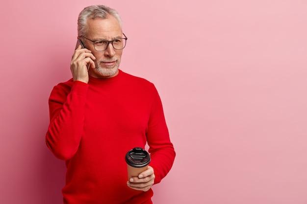 Starszy mężczyzna ubrany w czerwony sweter i rozmawia przez telefon
