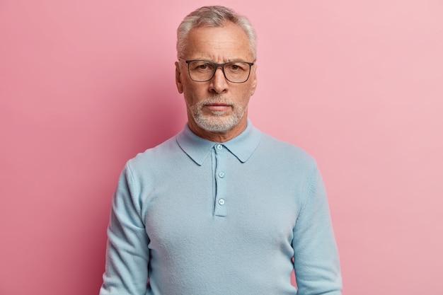 Starszy mężczyzna ubrany w niebieską koszulę i modne okulary
